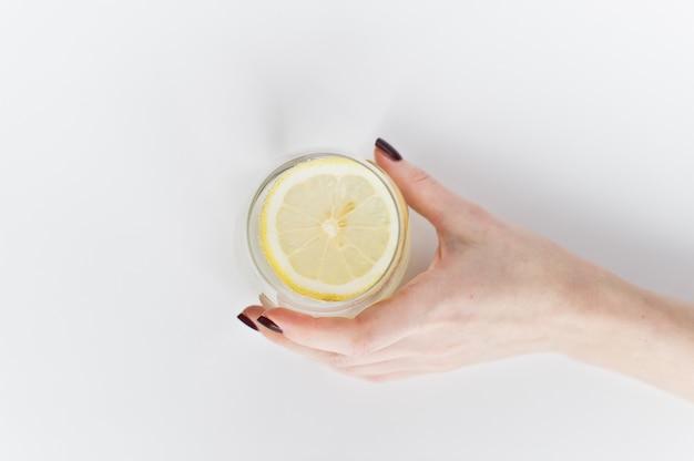 Mani in possesso di un bicchiere di acqua limpida con limone.