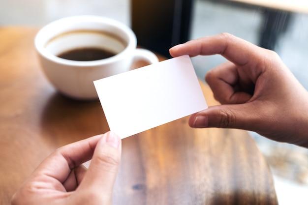 Mani in possesso di un biglietto vuoto con la tazza di caffè sul tavolo