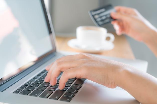 Mani in possesso di una carta di credito e utilizzando computer portatile per linea