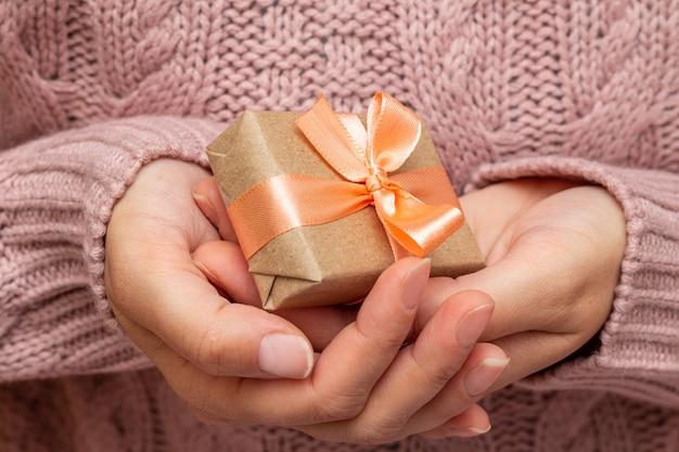 Mani in un maglione lavorato a maglia che tiene la confezione regalo. concetto di preparazione vacanze di natale.