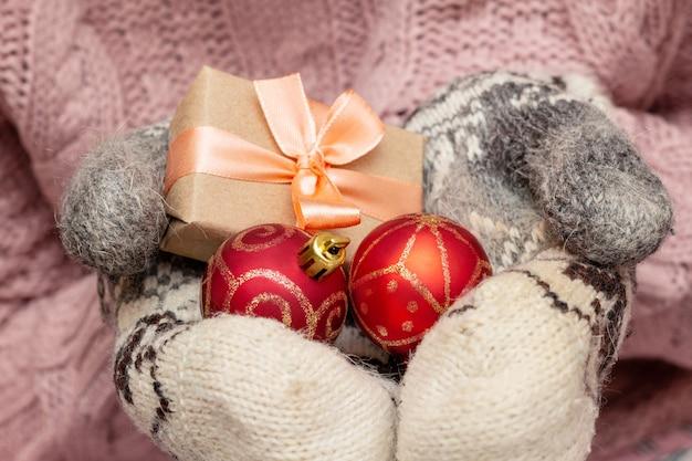 Mani in un maglione lavorato a maglia guanti tenendo presente confezione regalo. concetto di preparazione vacanze di natale.