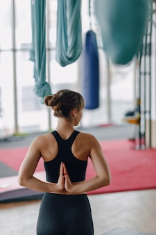 Mani incrociate dietro la schiena, ragazza in palestra durante la lezione di yoga