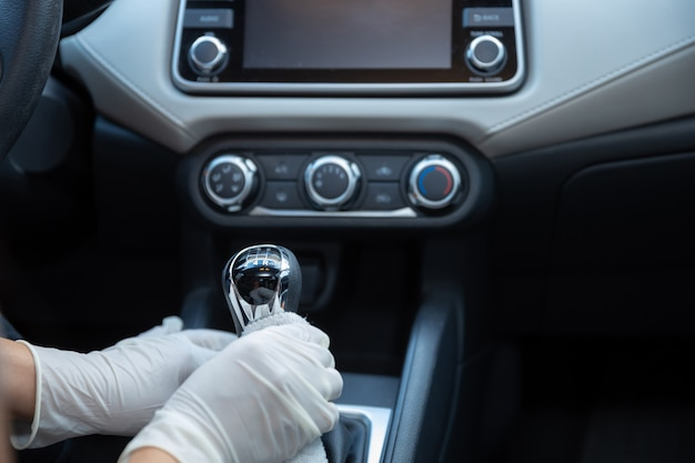 Mani inguantate che puliscono un'auto