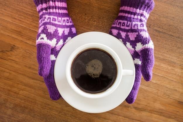 Mani inguantate che tengono tazza di caffè