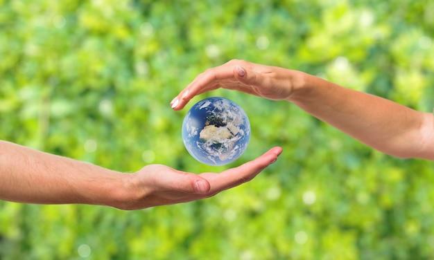 Mani intorno alla miniatura della terra