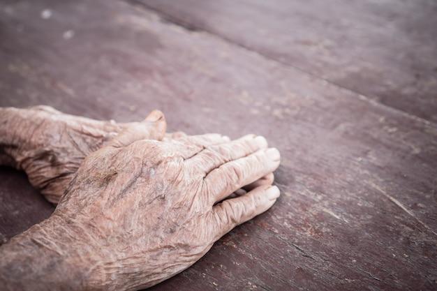 Mani la donna anziana asiatica afferra le sue mani in grembo