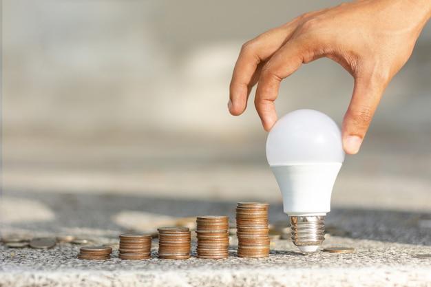 Mani maschii che mettono affare crescente della pila della moneta della lampadina del led