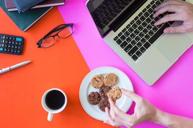 Mani maschii che tengono i biscotti e che utilizzano computer portatile, tazza di caffè e articoli per ufficio sulle sedere variopinte