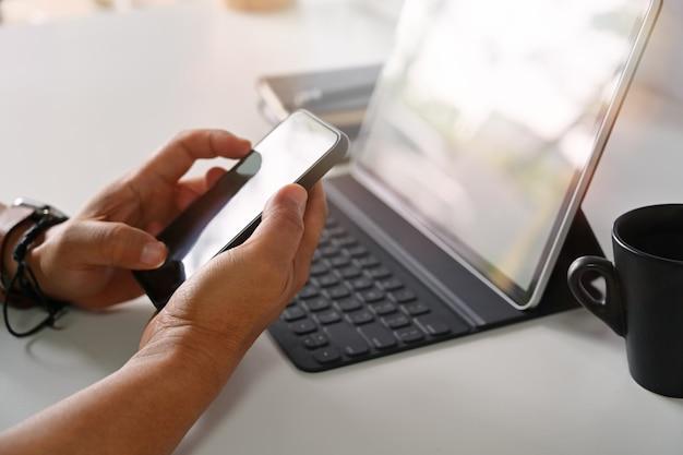 Mani maschii che tengono smartphone mobile sul posto di lavoro