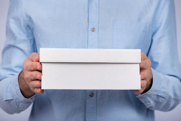 Mani maschii che tengono una scatola di cartone. avvicinamento. vista frontale. consegna espressa. il postino ha portato un pacco.