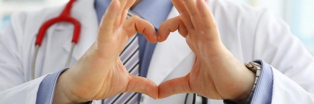 Mani maschii di medico della medicina che mostrano a forma di cuore