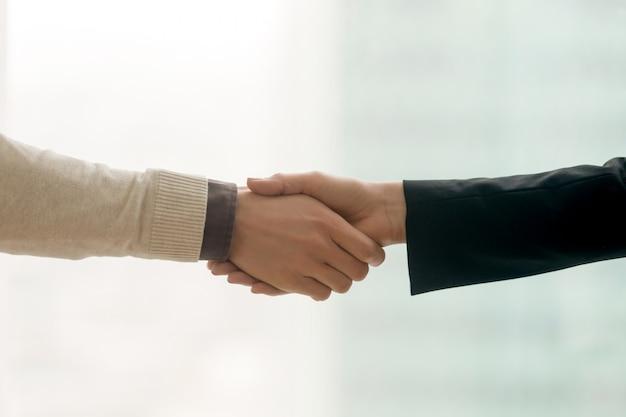 Mani maschii e femminili che agitano, stretta di mano di affari con lo spazio della copia