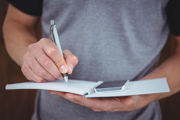 Mani maschili che scrivono sul taccuino
