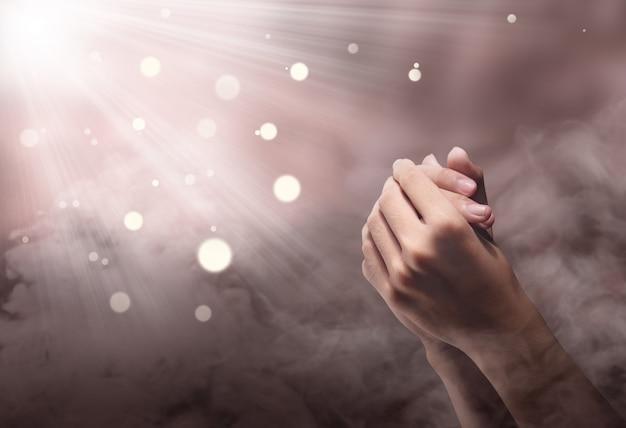 Mani maschili in posizione di preghiera con raggio
