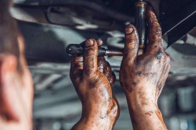 Mani maschili sporche con chiave dinamometrica. tecnico che ripara un'auto in un'officina