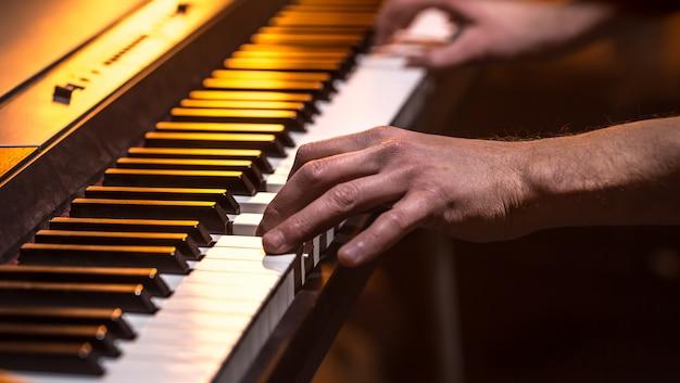 Mani maschili sui tasti del pianoforte