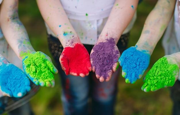 Mani / palme dei giovani coperte nei colori viola, gialli, rossi, blu di festival di holi isolati