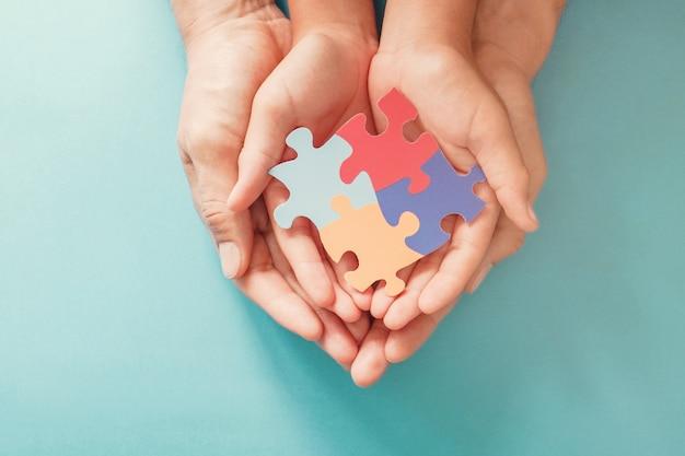 Mani per adulti e bambini che tengono forma di puzzle, consapevolezza dell'autismo, concetto di sostegno della famiglia dello spettro autistico, giornata mondiale della consapevolezza dell'autismo