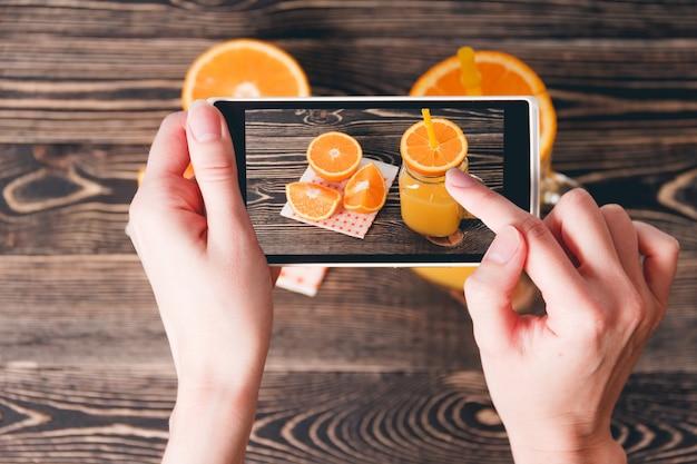 Mani prendendo foto di arance. concetto di tecnologia