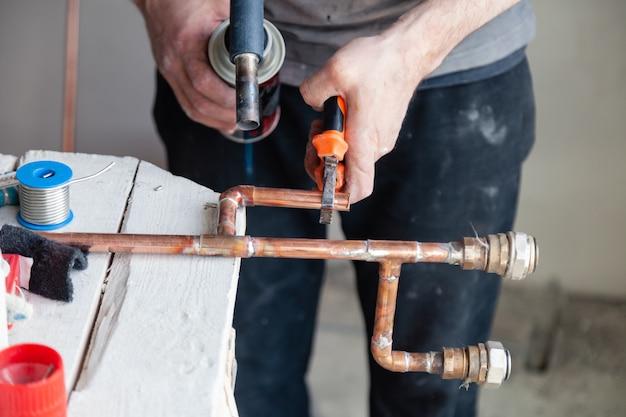 Mani professionali dell'idraulico principale del primo piano che saldano il bruciatore a gas dei tubi di rame.