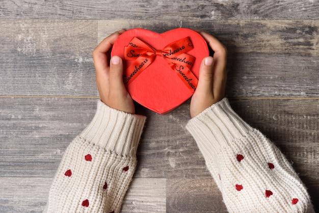 Mani ragazza poco in possesso di regalo a forma di cuore