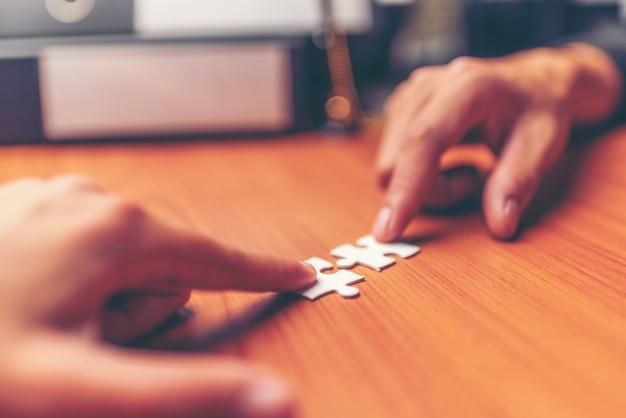 Mani ritagliate di uomini d'affari che si uniscono a pezzi di puzzle