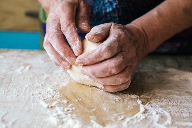 Mani rugose di una donna anziana che impasta la pasta