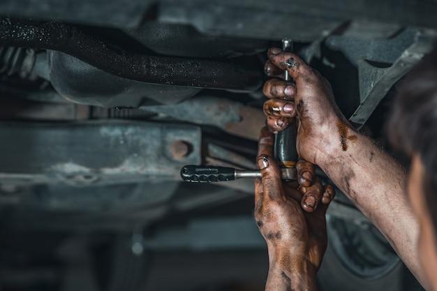 Mani sporche di un tecnico durante la riparazione di un'auto