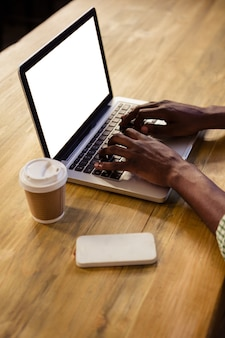 Mani sul computer portatile che scrivono insieme