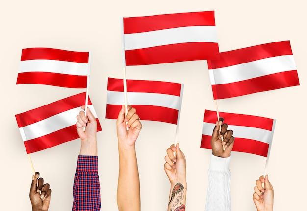 Mani sventolando bandiere d'austria