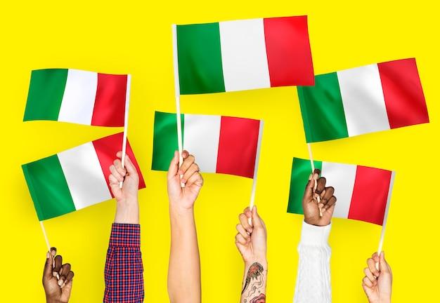 Mani sventolando bandiere d'italia