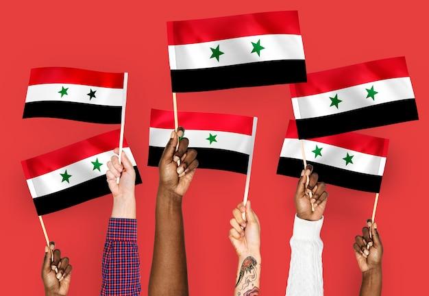 Mani sventolando bandiere della siria