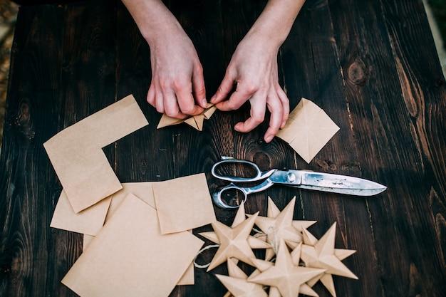 Mani umane che fanno stelle da carta kraft su uno sfondo di tavolo in legno marrone scuro