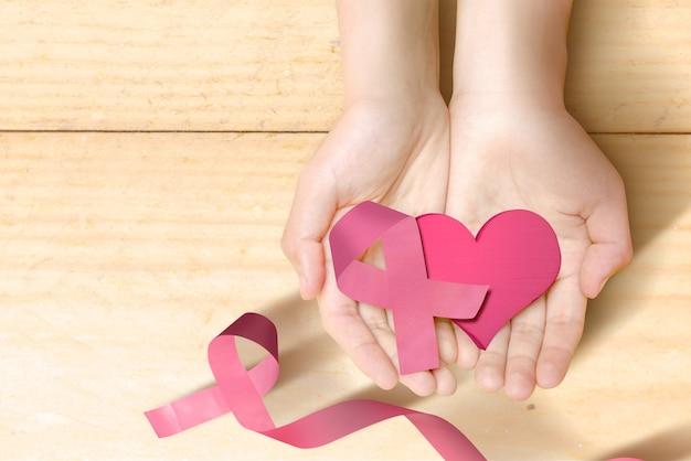 Mani umane che mostrano un cuore rosa con un nastro rosa su un fondo di legno