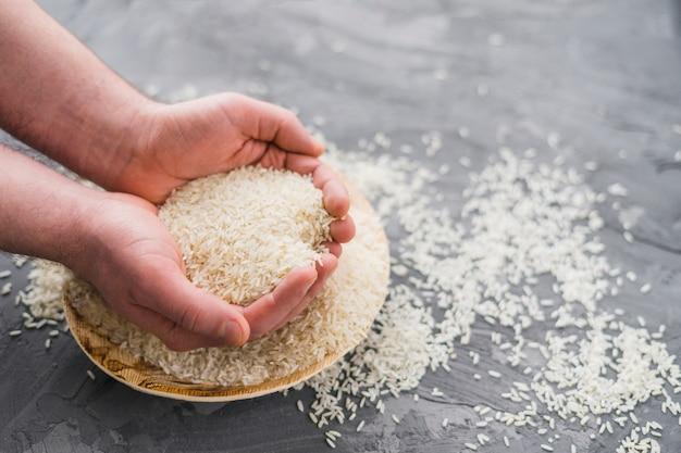 Mani umane che selezionano il riso dal piatto di legno sopra fondo concreto