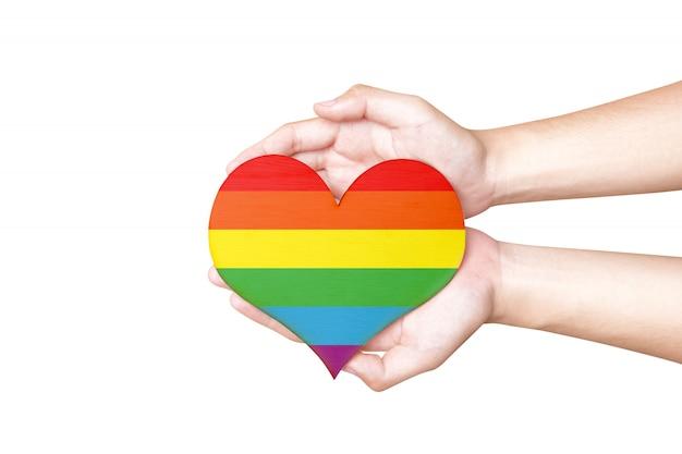 Mani umane che tengono il cuore con la bandiera arcobaleno come simbolo di lgbt