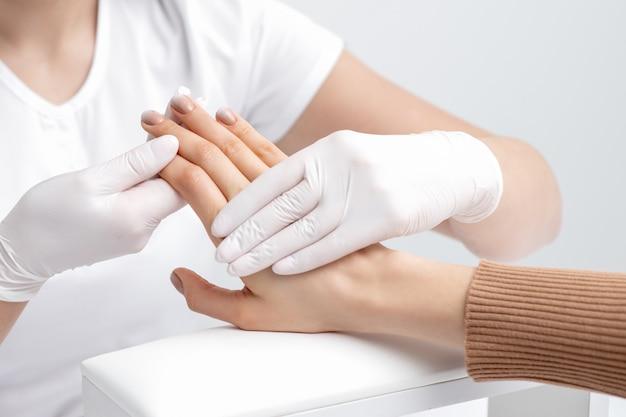 Mani umane che tengono le unghie femminili