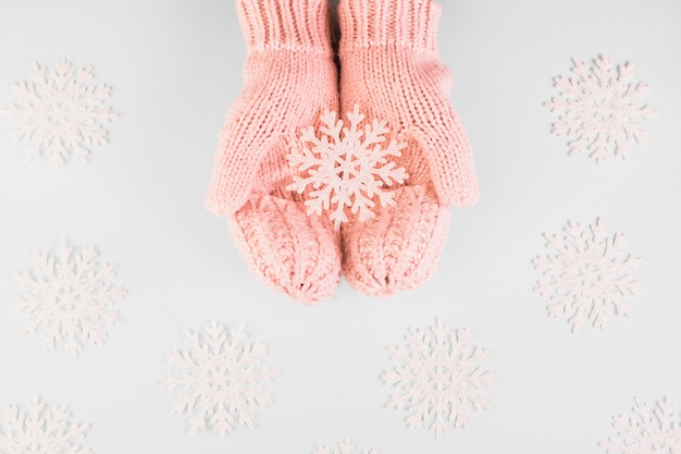 Mani umane in muffole con fiocco di neve di carta