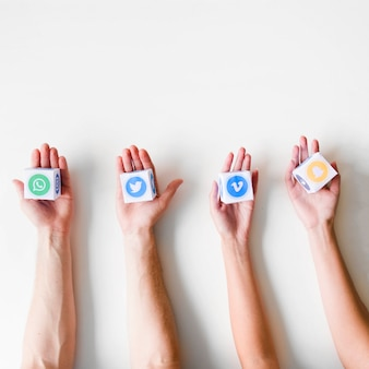 Mani umane in una riga che tiene le scatole di varie icone di applicazioni mobili