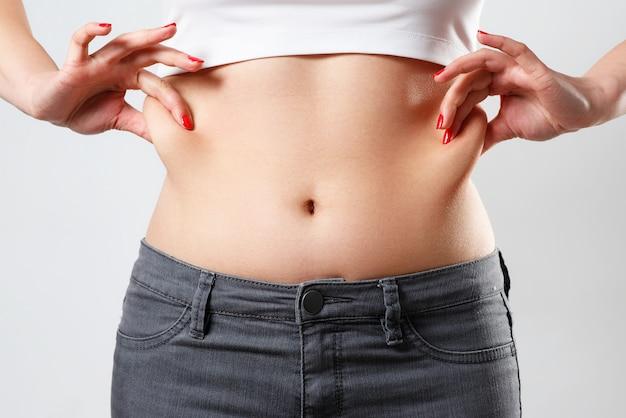 Mani una donna tiene una piega di grasso in eccesso sullo stomaco. su bianco