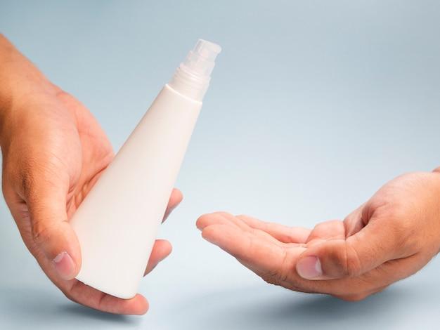 Mani usando la bottiglia di lozione mock-up