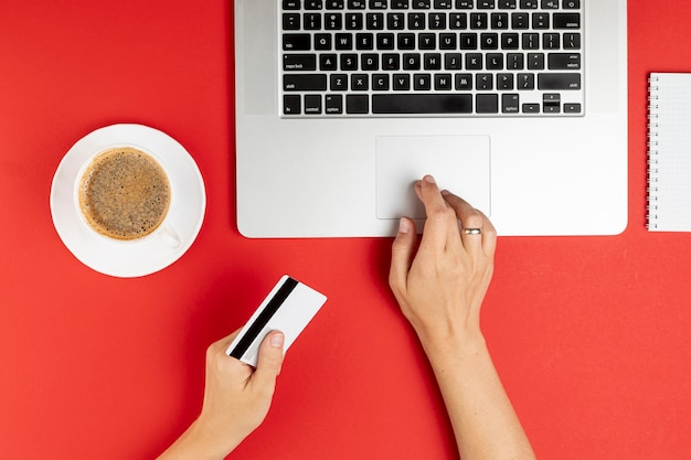 Mani utilizzando il computer e in possesso di una carta