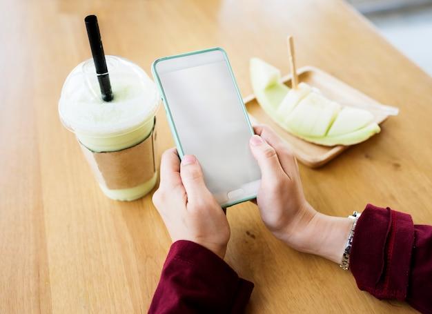 Mani utilizzando il telefono cellulare con frutta e bevande sul tavolo