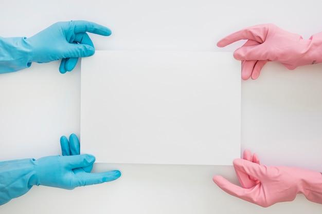 Mani vista dall'alto con guanti di gomma colorati
