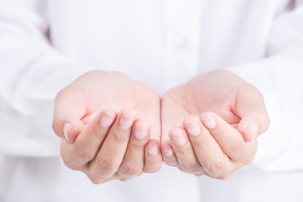 Mani vuote della bella donna che tengono con lo spazio aperto isolato su fondo bianco