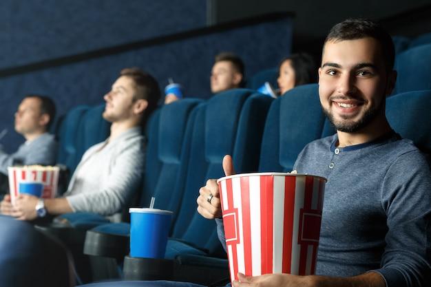 Mania del film. giovane uomo barbuto bello che mostra i pollici su che si siedono nel cinema che tiene il suo popcorn