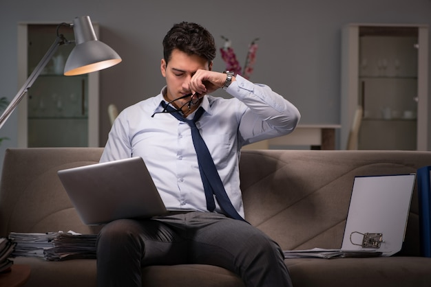 Maniaco del lavoro dell'uomo d'affari che lavora tardi a casa