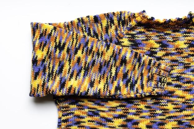 Manica lavorata a maglia su un maglione lavorato a maglia, colore blu giallo nero marrone.