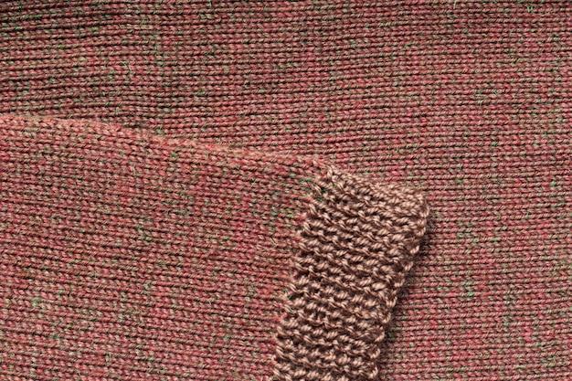 Manica marrone lavorata a maglia su uno sfondo marrone lavorato a maglia.