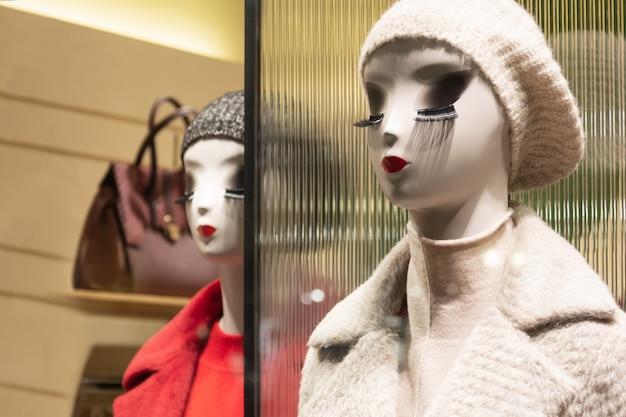 Manichini nel negozio con labbra vivaci e lunghe ciglia dimostrano abbigliamento invernale.